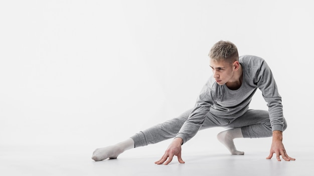 Front view of male dancer in tracksuit and socks posing while dancing