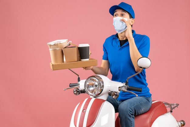 Front view of male delivery person in mask wearing hat sitting on scooter delivering orders calling someone on peach background