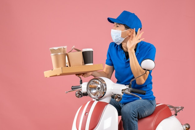 Front view of male delivery person in mask wearing hat sitting on scooter delivering orders listening to the last gossiping on pastel peach background