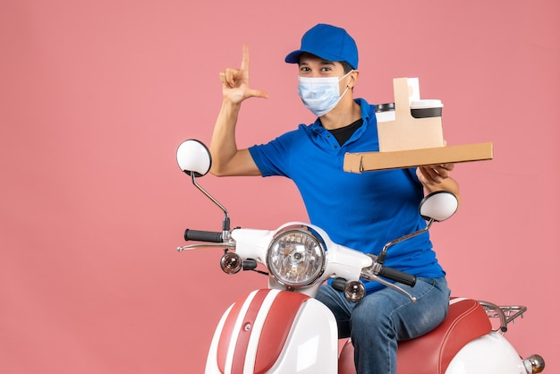 Front view of male delivery person in mask wearing hat sitting on scooter delivering orders making exact something on pastel peach background