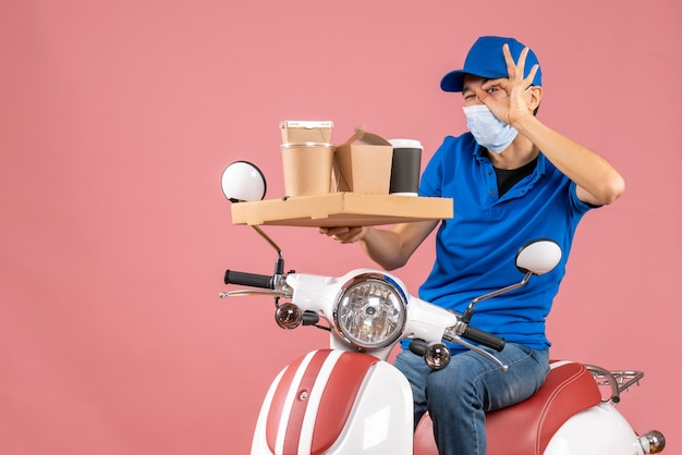 Front view of male delivery person in mask wearing hat sitting on scooter delivering orders making eyeglasses gesture on pastel peach background