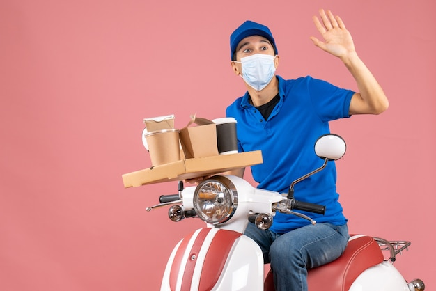 Front view of male delivery person in mask wearing hat sitting on scooter delivering orders on pastel peach background
