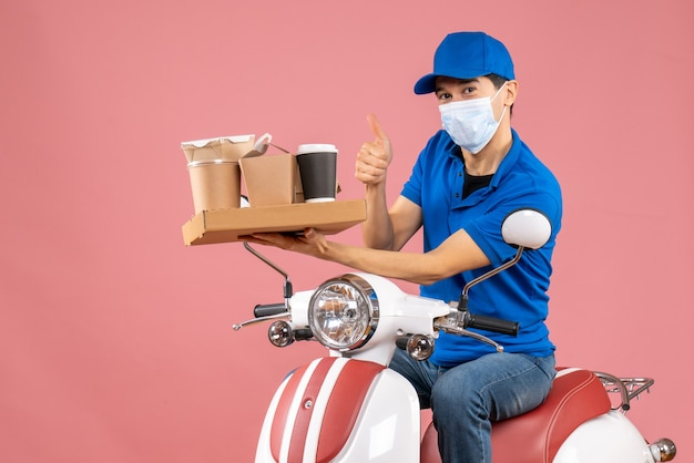 Front view of male delivery person in mask wearing hat sitting on scooter delivering orders on peach background