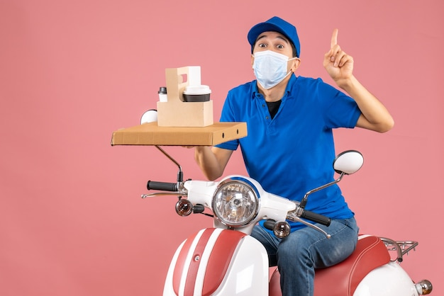 Front view of male delivery person in mask wearing hat sitting on scooter delivering orders pointing up on pastel peach background