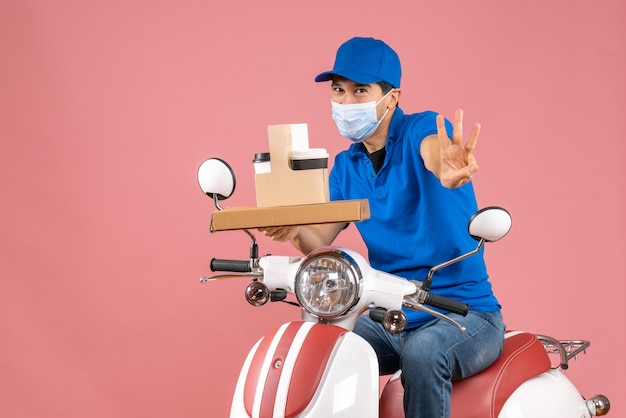 Front view of male delivery person in mask wearing hat sitting on scooter delivering orders showing three on pastel peach background