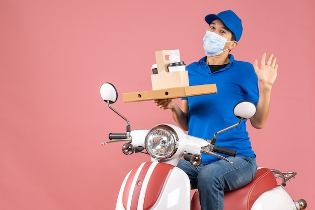 Front view of male delivery person in mask wearing hat sitting on scooter showing orders on pastel peach background