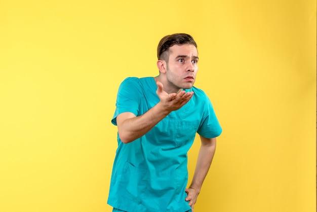 Vista frontale del medico maschio che discute sulla parete gialla