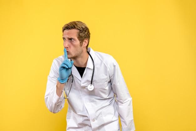 Medico maschio di vista frontale che chiede di essere tranquillo sul medico del virus umano di salute del fondo giallo