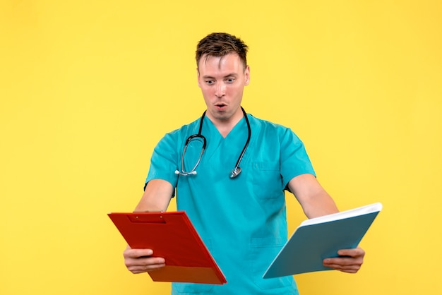 Front view of male doctor checking analyzes on yellow wall