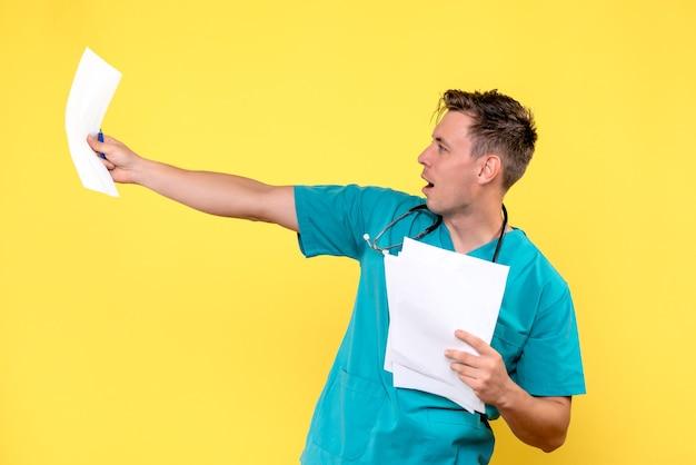 Vista frontale del medico maschio che controlla i documenti sulla parete gialla