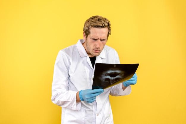 Medico maschio di vista frontale che controlla i raggi x del cranio sulla chirurgia del medico della scrivania gialla covid-