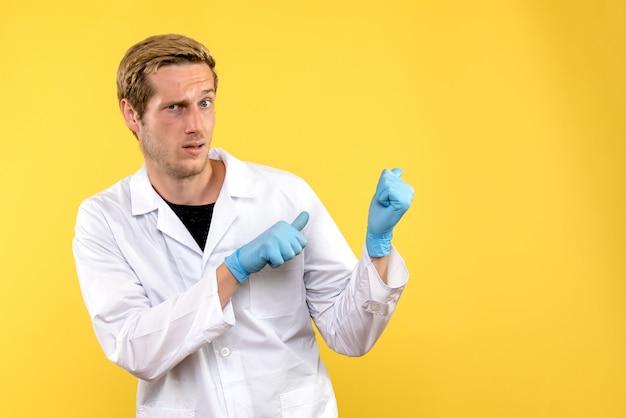 Вид спереди мужской доктор смущен на желтом фоне covid- человеческий медик