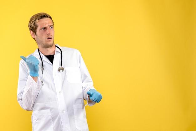 Вид спереди мужской доктор смущен на желтом фоне здоровья медика человеческого вируса