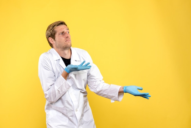 Front view male doctor confused on the yellow background covid- pandemic health medic