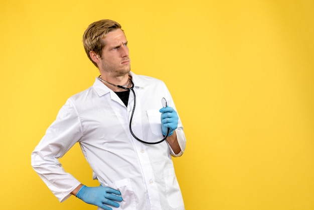 Front view male doctor confused on yellow background health virus medic emotion