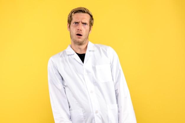 Vista frontale medico maschio confuso su sfondo giallo medico pandemia umana covid