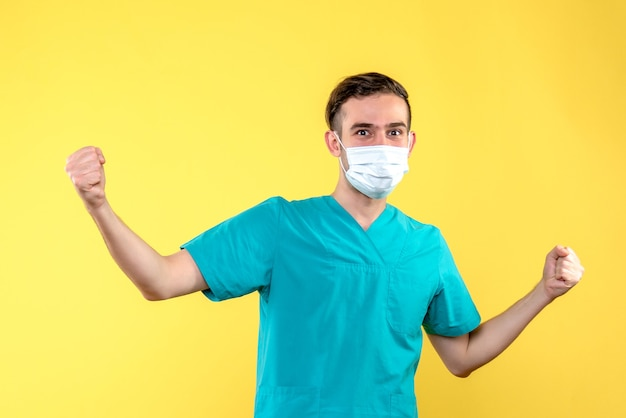 Vista frontale del medico maschio che gioisce in maschera sulla parete gialla