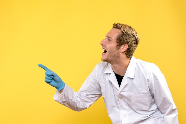 Front view male doctor excited on a yellow background covid- hospital medic human