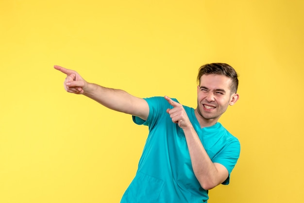Front view of male doctor excited on yellow wall
