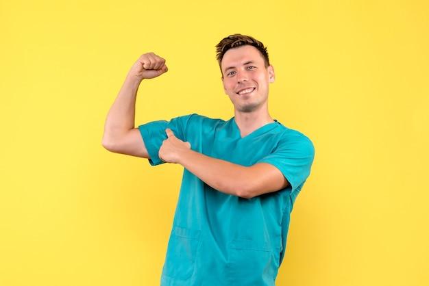 Vista frontale del medico maschio che flette e sorride sulla parete gialla