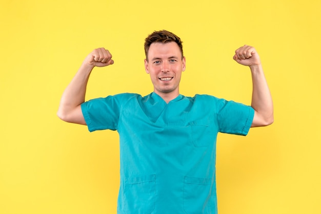 Front view of male doctor flexing with smile on yellow wall