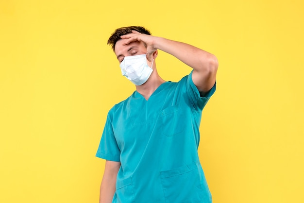 Front view of male doctor having severe headache on yellow wall