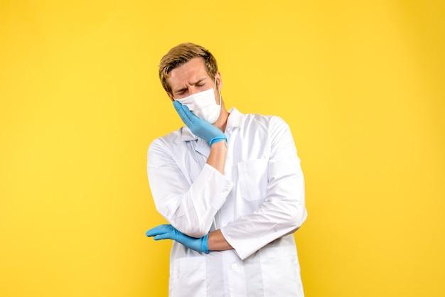 Вид спереди мужчина-врач с зубной болью на желтом фоне пандемический вирус здоровья