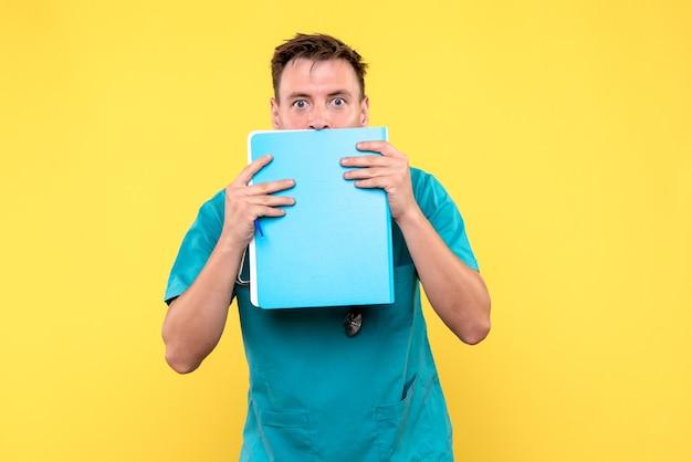Vista frontale del medico maschio che tiene analisi in file sulla parete gialla