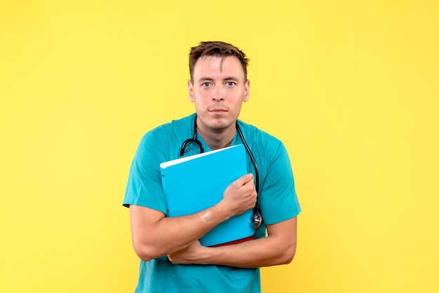 Front view of male doctor holding analyzes on light yellow wall