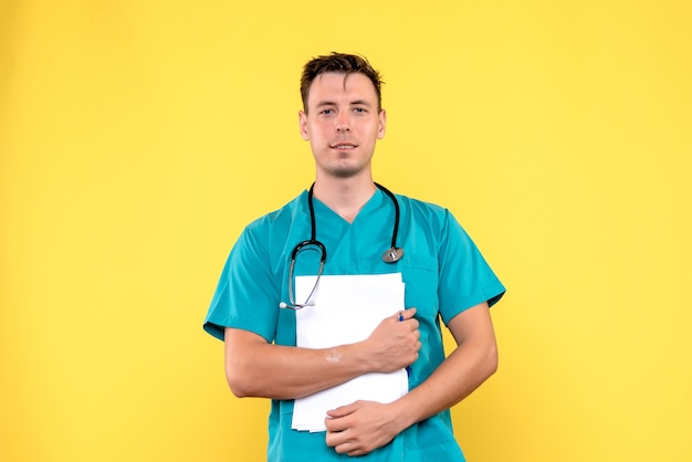 Front view of male doctor holding analyzes on yellow floor medical emotion hospital