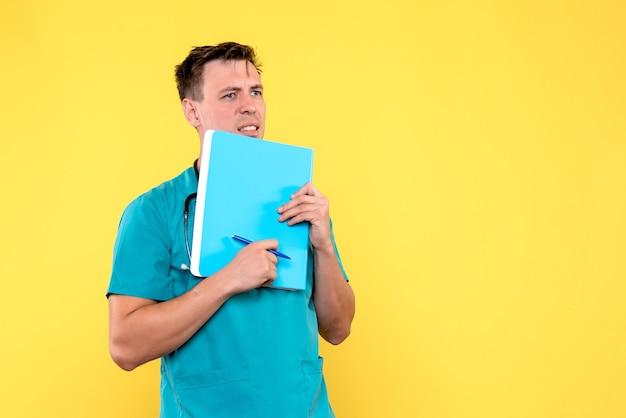 Vista frontale del medico maschio che tiene analisi sulla parete gialla