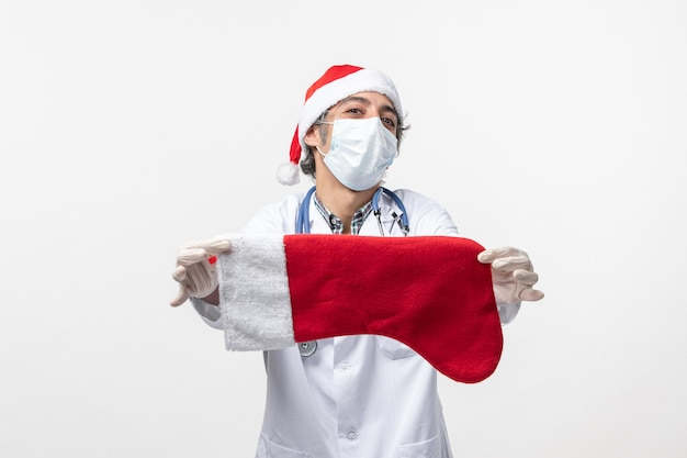 白い壁のcovidウイルスの休日に大きな休日の靴下を保持している正面図男性医師