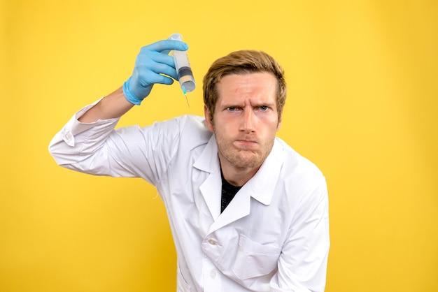 黄色の背景に大きな注射をしている正面図の男性医師メディックコビッドウイルス