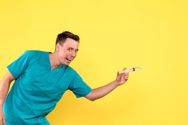 Vista frontale del medico maschio che tiene grande iniezione sulla parete gialla