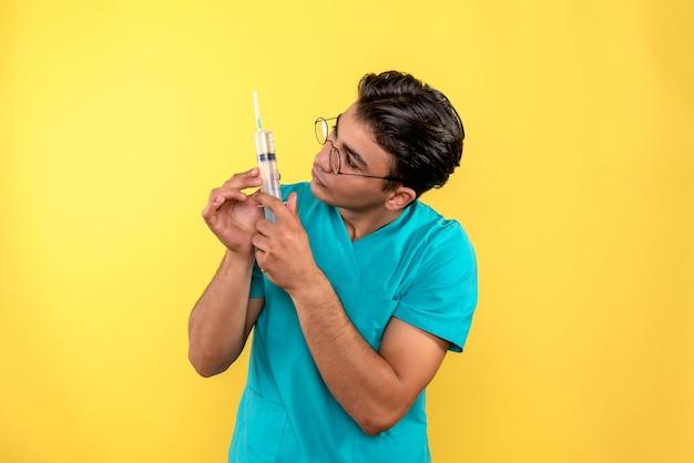 Vista frontale del medico maschio che tiene una grande iniezione
