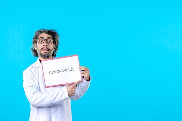 Medico maschio di vista frontale che tiene la scrittura del coronavirus sul blu