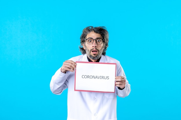 Front view male doctor holding coronavirus writing on blue