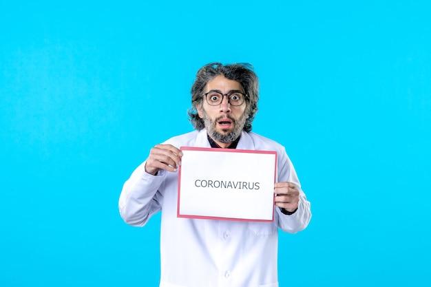 파란색에 코로나바이러스 쓰기를 들고 전면 보기 남성 의사