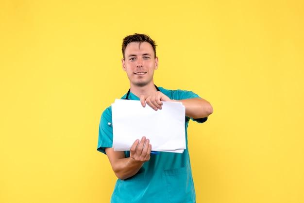 Vista frontale del medico maschio che tiene i documenti sulla parete gialla