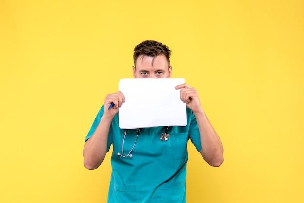 Vista frontale del medico maschio che tiene i file sulla parete giallo chiaro