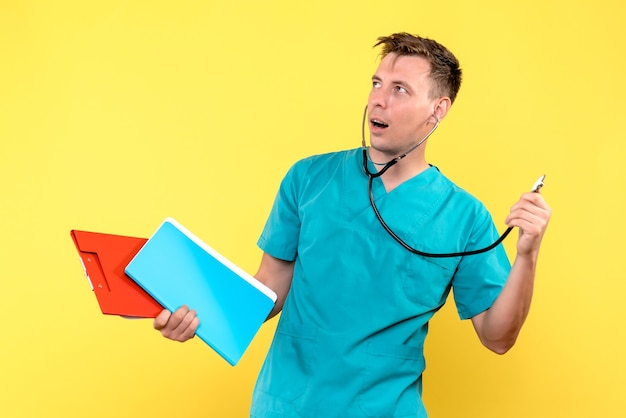Front view of male doctor holding files and tonometer on yellow wall