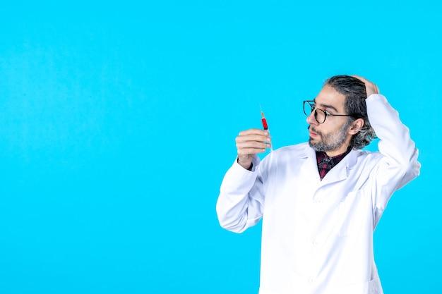 파란색에 주사를 들고 전면 보기 남성 의사
