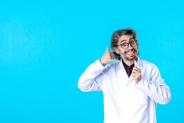 Front view male doctor holding injection smiling on blue