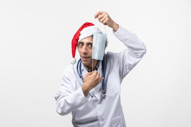Maschera della tenuta del medico maschio di vista frontale sul virus di festa del nuovo anno covid della parete bianca