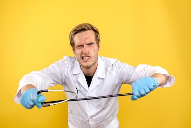 Вид спереди мужской доктор, держащий стетоскоп на желтом фоне, здоровье человека, covid- medic