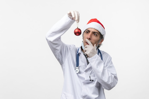 白い壁のウイルスcovid健康新年におもちゃを保持している正面図男性医師