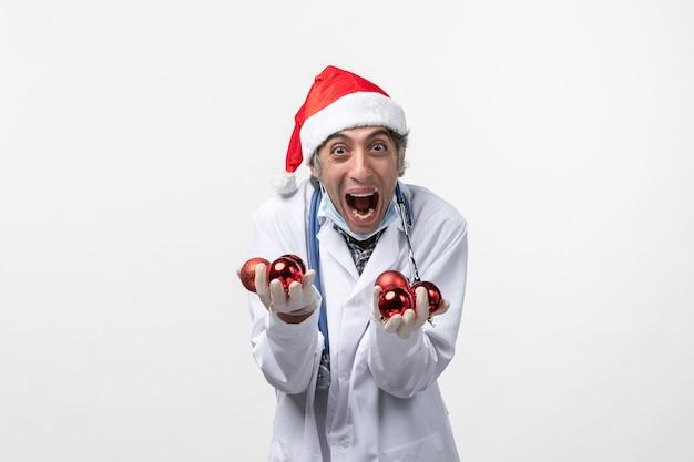 白い机の上におもちゃを持っている正面図男性医師covid-健康ウイルスの感情