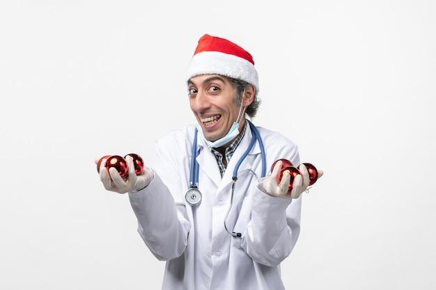 白い机の上のおもちゃを持っている正面図の男性医師ウイルスcovid感情の健康