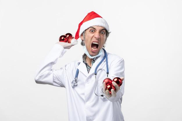 白い壁のウイルスのcovid感情の健康におもちゃを保持している正面図男性医師
