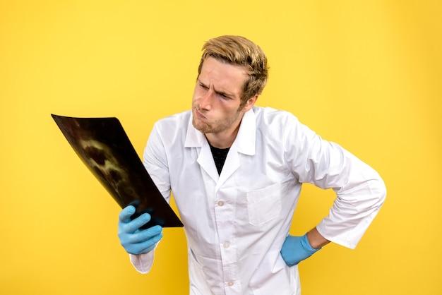 노란색 배경 수술 의료진 covid 위생에 엑스레이를 들고 전면보기 남성 의사